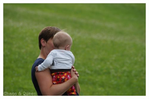 Mutter mit Kind vor grüner Wiese