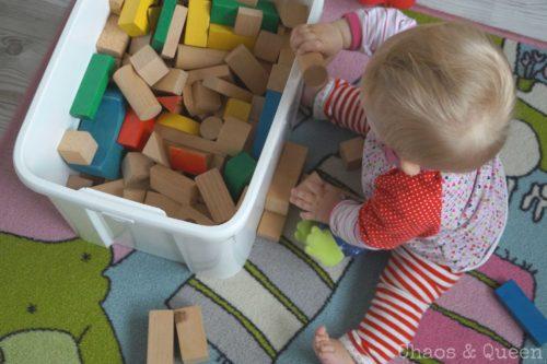Baby sitzt und spielt mit Bauklötzen
