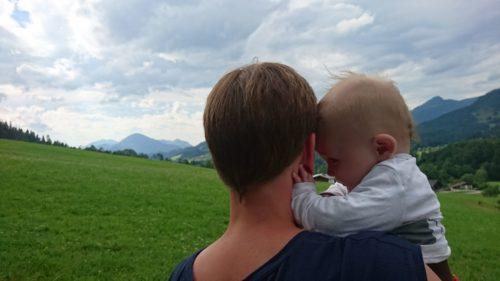 Mutter mit Baby vor Bergkulisse
