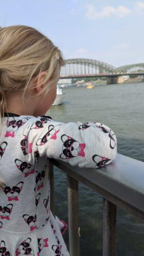 Mädchen schaut in Köln auf den Rhein