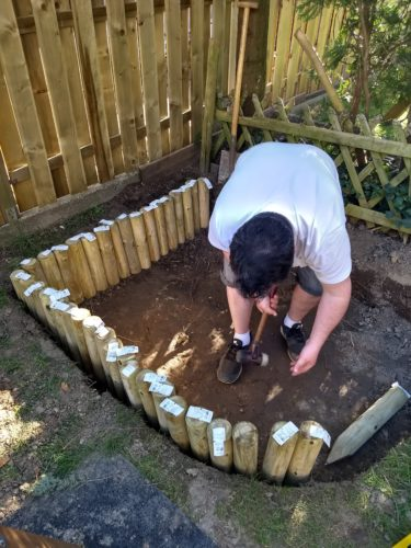 Sandkasten bauen mit Rundholzpalisaden