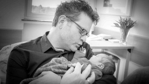 Vater mit Neugeborenem im Arm